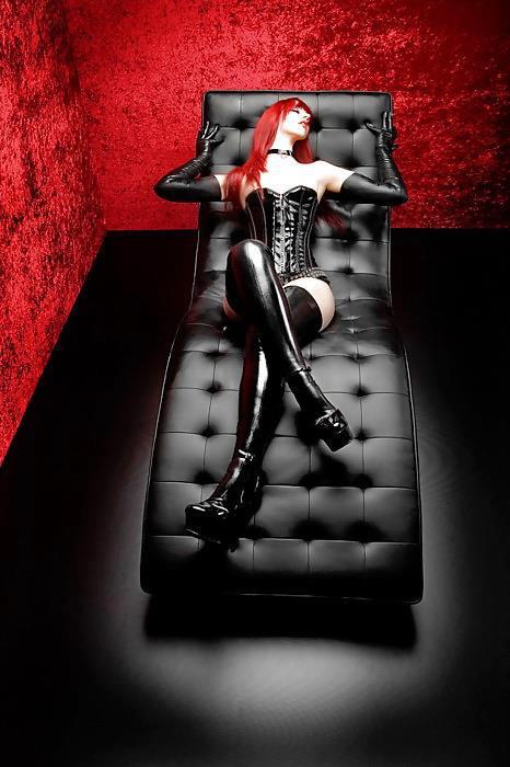 mistress dai capelli rossi vestita in latex stivali compresi